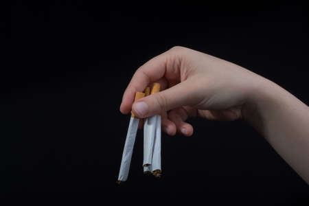 Hand is holding cigarettes on black background Stock Photo