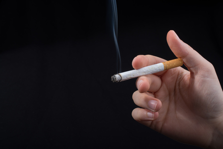 Hand is holding smoking cigarette with smoke around Stock Photo