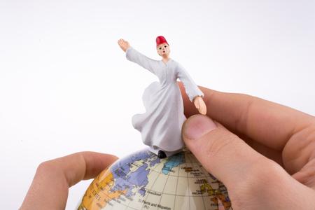 Hand holding a Sufi Derviş on a globe Stock Photo