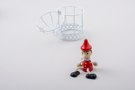 Metal cage and Little puppet pinocchio made of wood Standard-Bild
