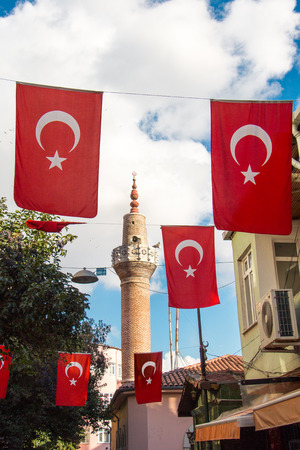 Turkish national flag hang on a pole on a rope with a minaret behind Stock Photo