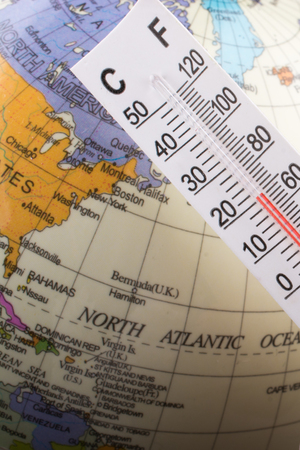 Hand placing a thermometer on a little model globe Standard-Bild