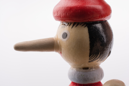 Wooden pinocchio doll with his long nose on a white background