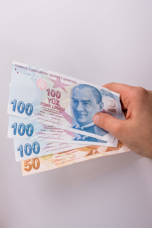 Hands holding American dollar banknotes and Turksh Lira banknotes side by side on white background