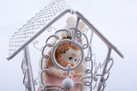 Little baby figure in a cage on a white background