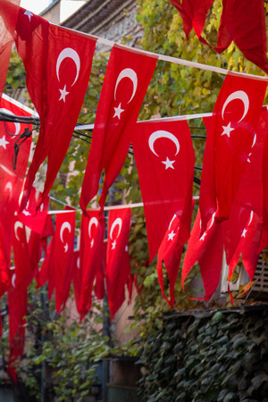 Turkish national flag hang on a pole on a rope in the street in open air Stock Photo