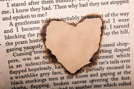 Heart shaped burnt out of a texted paper Stock Photo