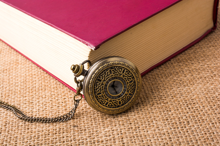 Retro style pocket watch beside a book on a canvas