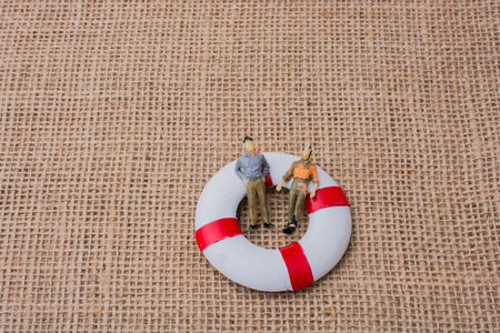 Little figurine men in a life preserver on life on canvas Stock Photo
