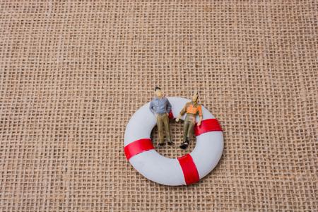 Pequeños hombres figurillas en un salvavidas sobre la vida sobre lienzo