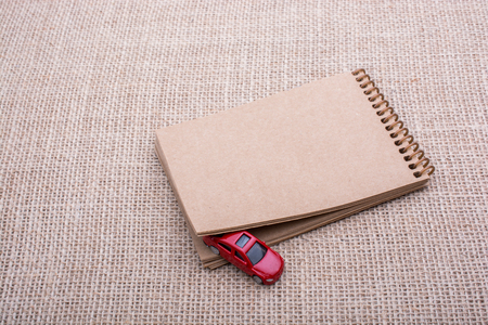 Red toy car coming out of a notebook on a linen canvas Stock Photo
