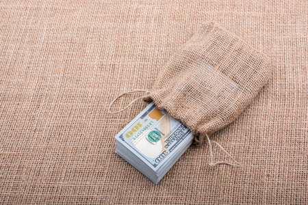 Banknote bundle of US dollarin a sack on a canvas