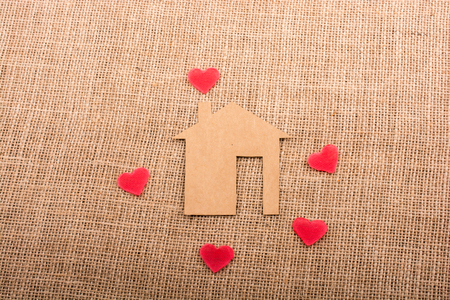 Heart shape around the  paper house with a canvas background