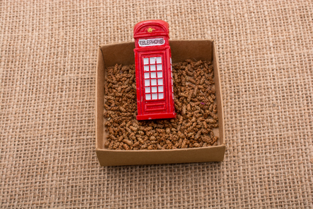 Red color phone booth in a box on a canvas background
