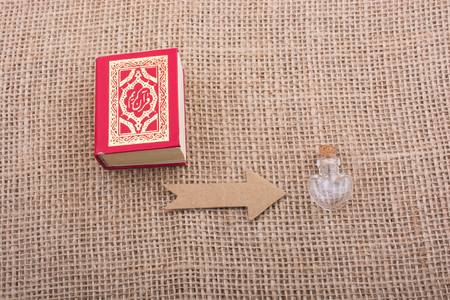 Paper  arrow and  Islamic Holy Book Quran in mini size Stock Photo