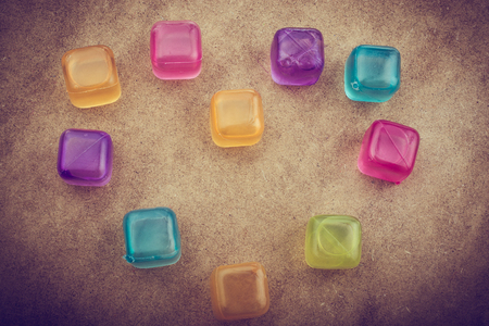 Fake colorful ice cubes on a brown background