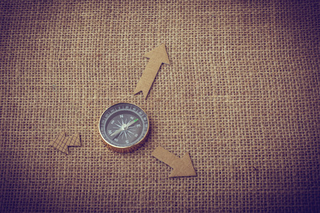Compass and  paper arrow on a canvas background