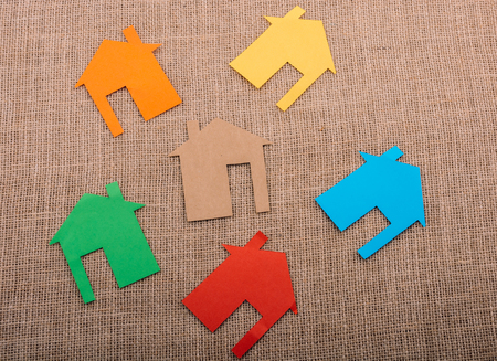 Little house shape cut out of colorful paper on a canvas background