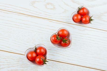 Red ripe cherry tomatos  tomatos in heart shaped bowl