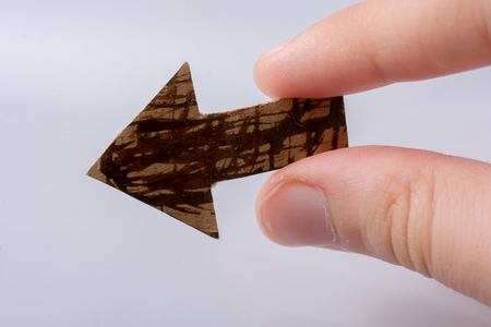 Arrow cut out of brown paper in hand on white Banque d'images