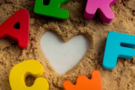 Heart shape and colorful Letters made of wood on sand