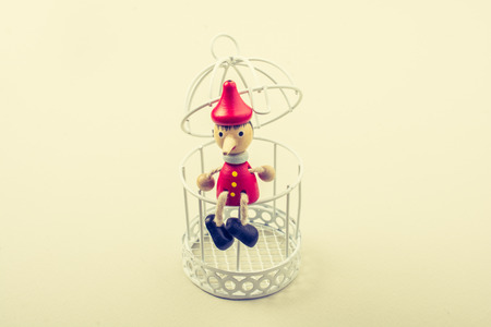 Metal cage and Little puppet pinocchio made of wood Stockfoto