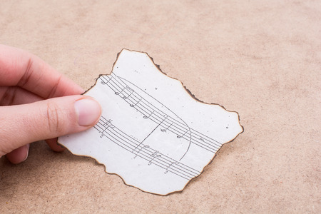 Hand holding a burnt paper with musical 免版税图像