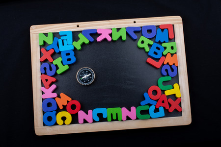 Compass and colorful letters of alphabet made of wood