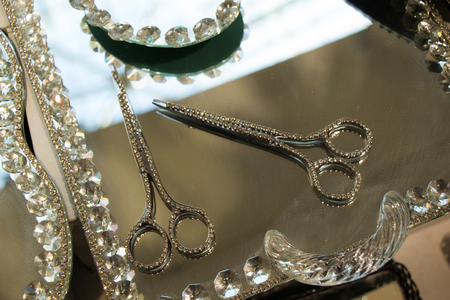 Metal scissors with diamonds on it on a mirror