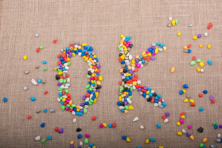 Colorful pebbles form the word OK on canvas ground