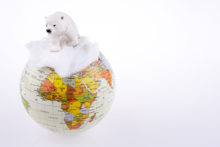 Polar bear on globe on a white background