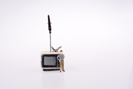 Man standing by a retro styled television set on a white background Banco de Imagens - 113130986