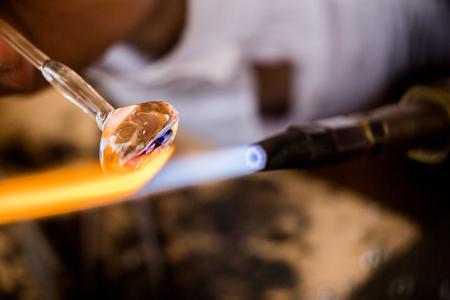 Hands of a man making a glass subject on display Standard-Bild