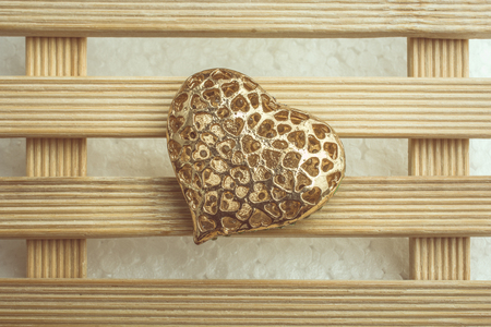 Gold color heart shaped l decorative object in view Reklamní fotografie