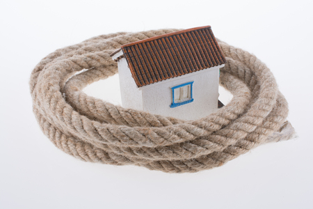 house surrounded by rope on a white background Фото со стока