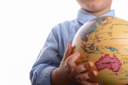 Baby with blue shirt holding a globe in hand on white background