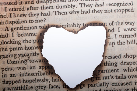 Hand holding a heart shaped burnt out of a texted paper