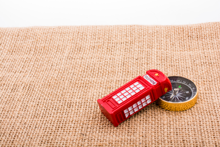 Compass and red color phone booth on canvas background