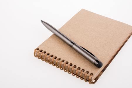 Spiral notebook and pollpoint pen on a white background
