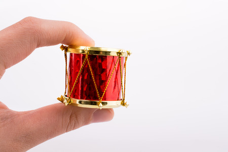 Hand holding a small drum on a white background