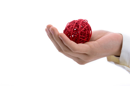 Hand holding a red spool of thread  on a white background