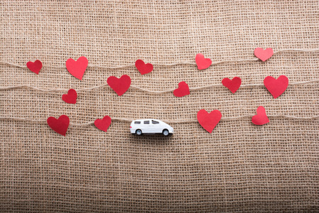 Love concept with car and paper heart on linen threads Imagens