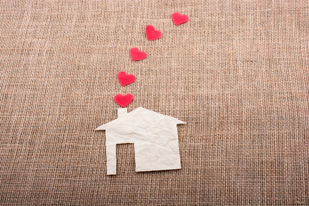 Heart shape coming out of chimney of paper house Imagens