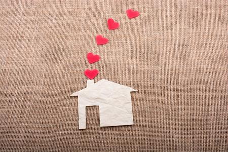Heart shape coming out of chimney of paper house Reklamní fotografie