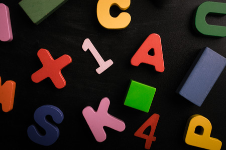 Wooden numbers, letters and blocks on a black background