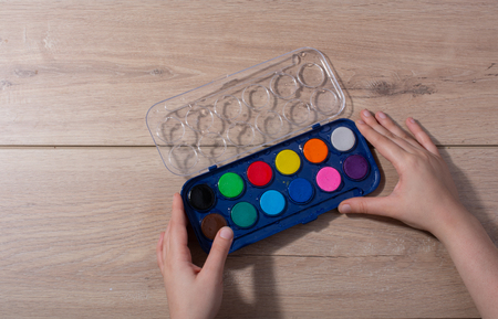 Hand holding a watercolor paint box on a wooden background