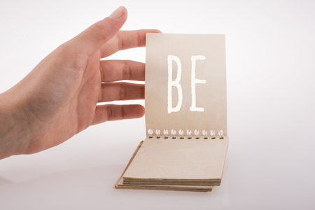 Hand holding notebook with be word on a white background