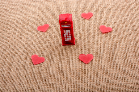 Red hearts around red color phone booth on canvas Stockfoto