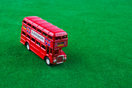 Red london bus on green grass