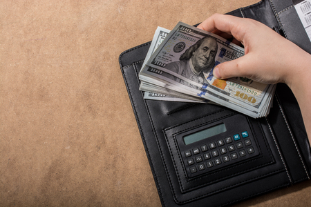 Hand holding American dollar banknotes beside a calculator